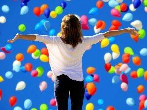 Frau tanzt mit Luftballons - Selbstbewusstsein
